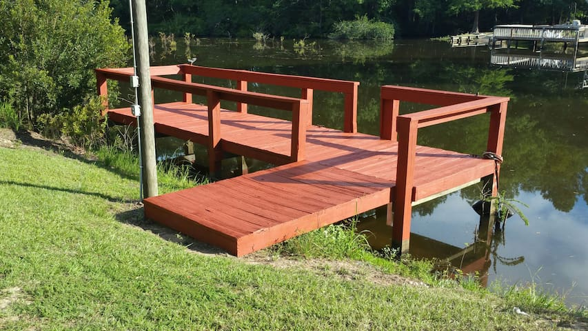 Cozy relaxing lake home with dock on wooded lot.