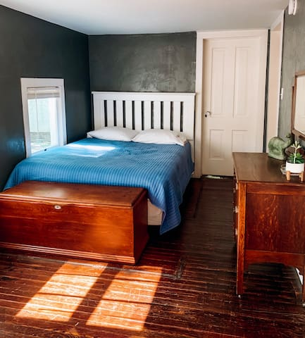 East Room - queen bed, dresser, reading chair and trunk.