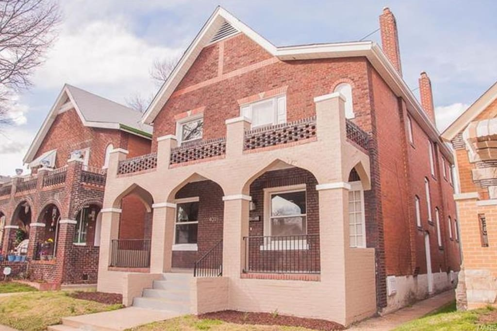 Grand brick facade with beautiful arches adorn the porch and upstairs balcony