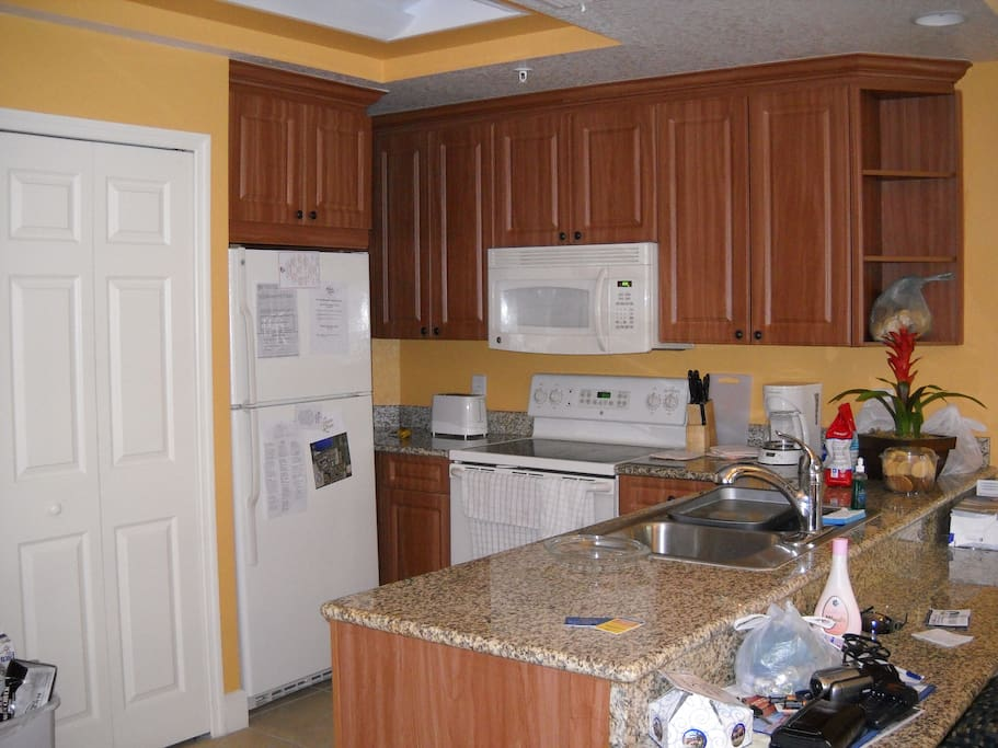 kitchen with washer + dryer behind closed door next to fridge