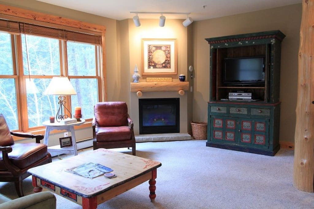The living room features a gas fireplace, flat screen TV, and beautiful views.