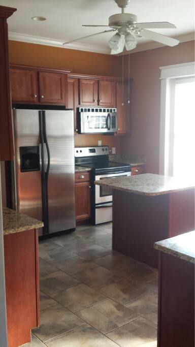Stainless appliances, granite tops tiled floors