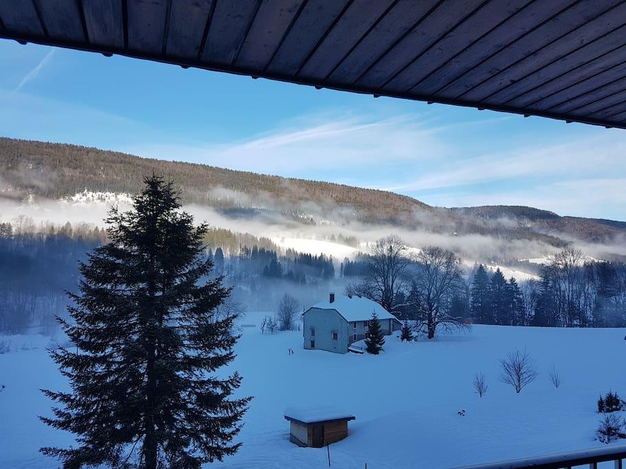 Vue hivernale imprenable sur les monts de la chaîne du Jura depuis le balcon du salon