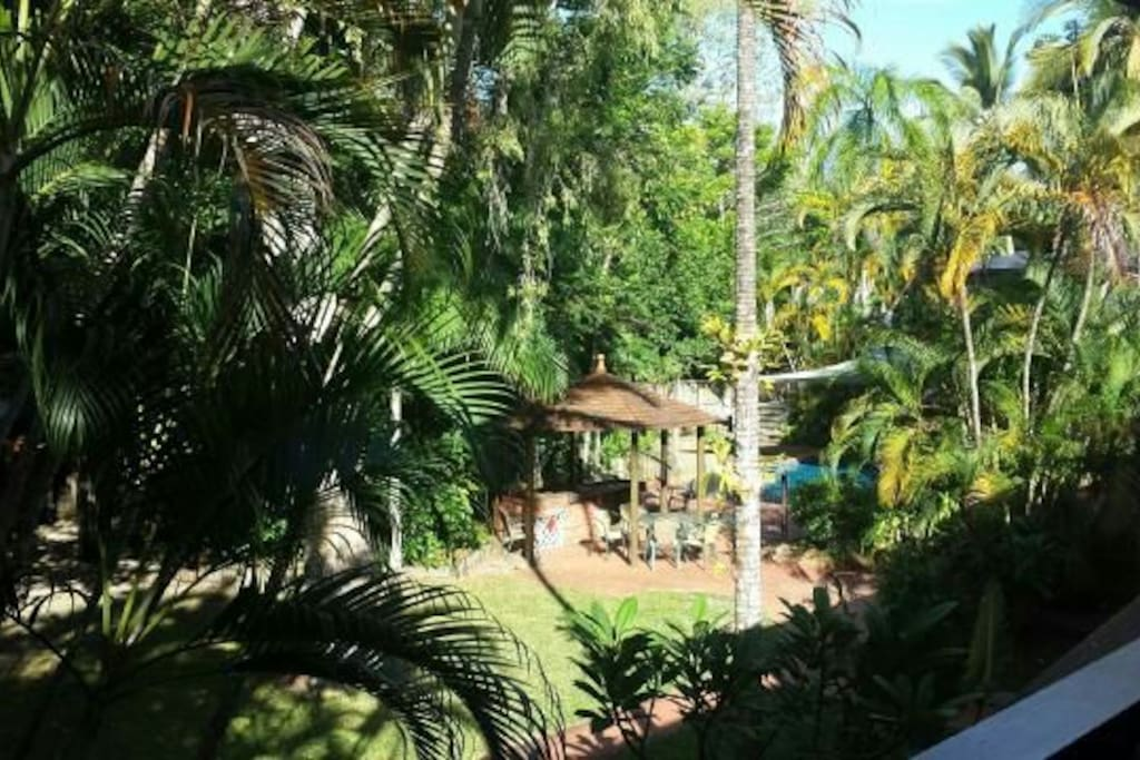 View from upstairs patio into the gardens and large saltwater pool & communal BBQ