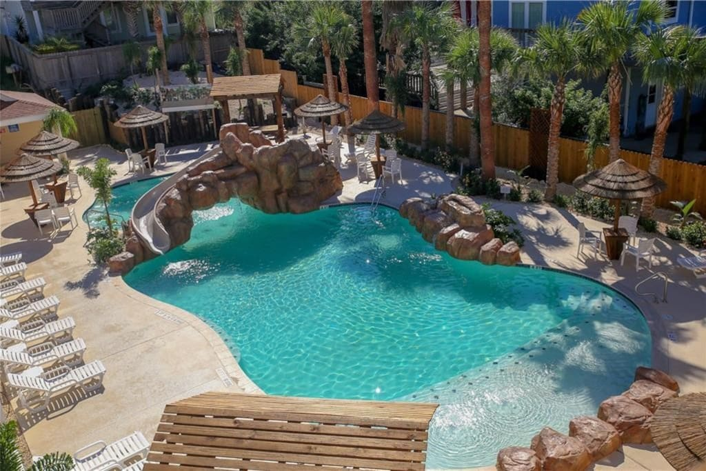 Resort pool with water slide and loungers