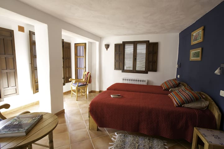 Veleta room with king size bed option (180x200) or two beds (90x200), private bathroom and a direct access to shared terrace