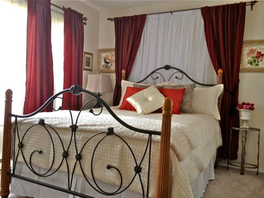 Romantic queen bed with plush duvet in your full sized suite.