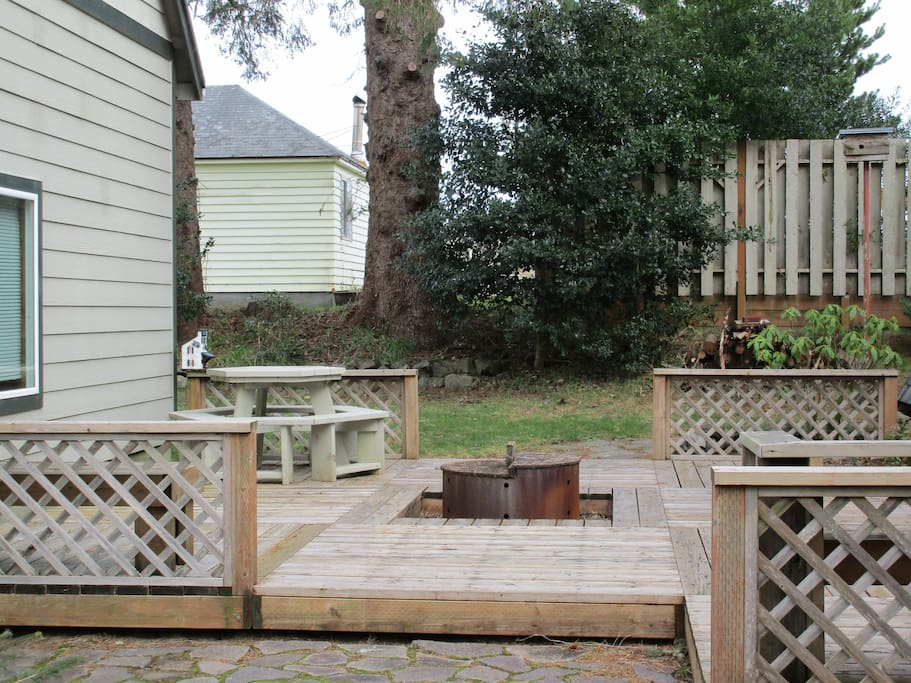 Firepit surrounded by the deck and picnic table