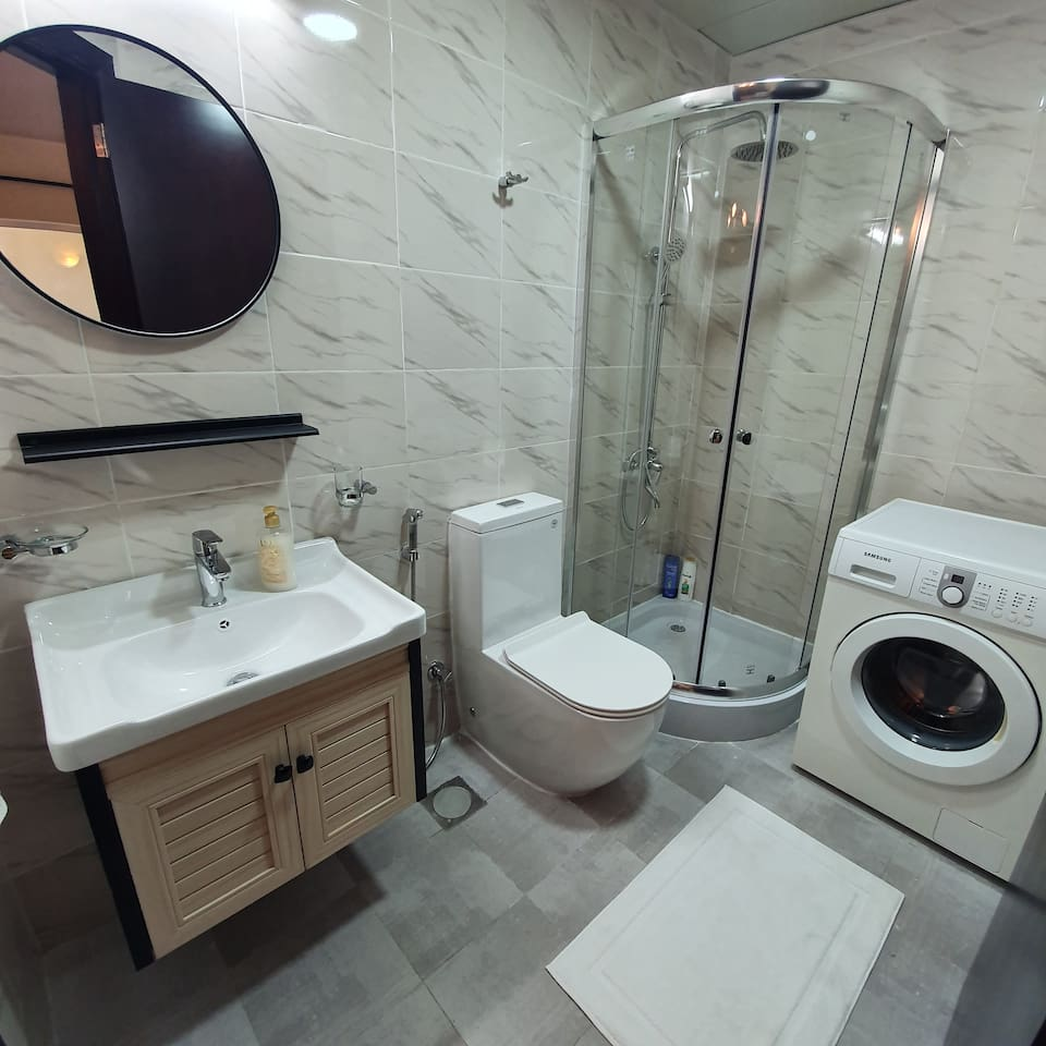 Completely renovated bathroom with shower cabin and washing machine