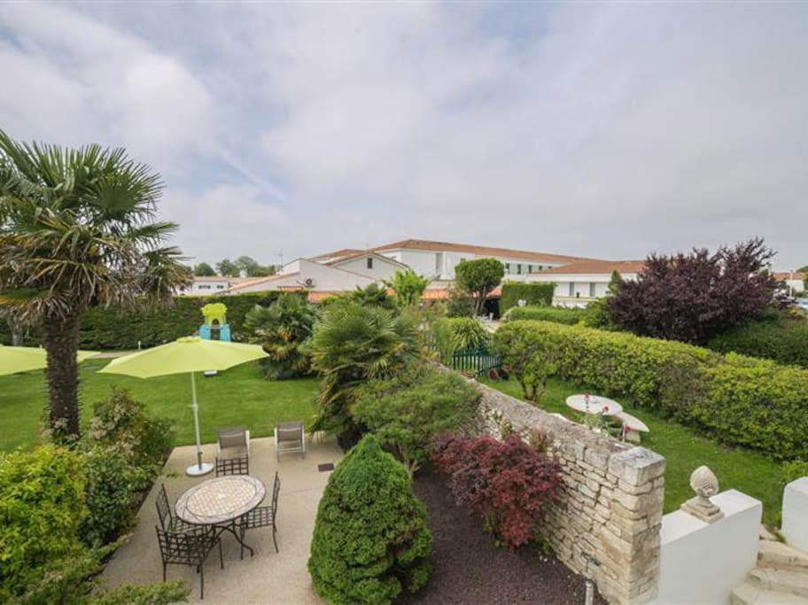 Terrasse privée avec salon de jardin, transats et parasol