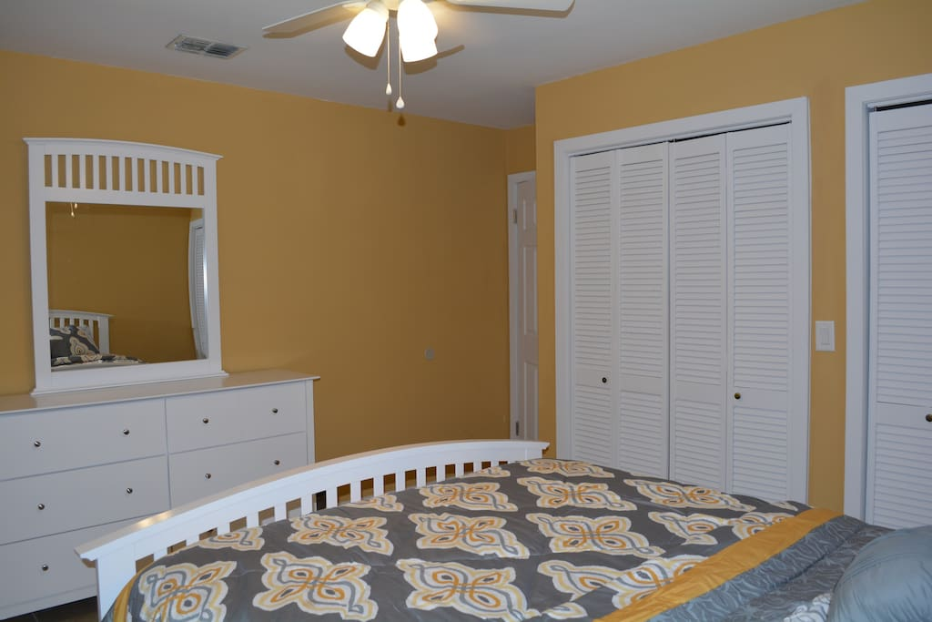 Master Bedroom with Queen bed, double closets, ceiling fan, and dresser.