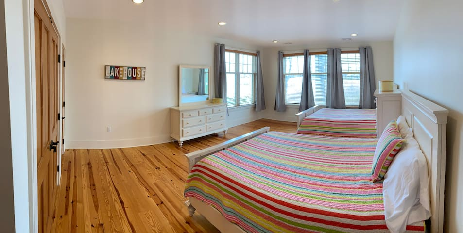 """Guest room located on the lower level of the house with 2 queen beds. This room has a very """"beachy"""" feel to it with its white furniture and large windows facing the water."""