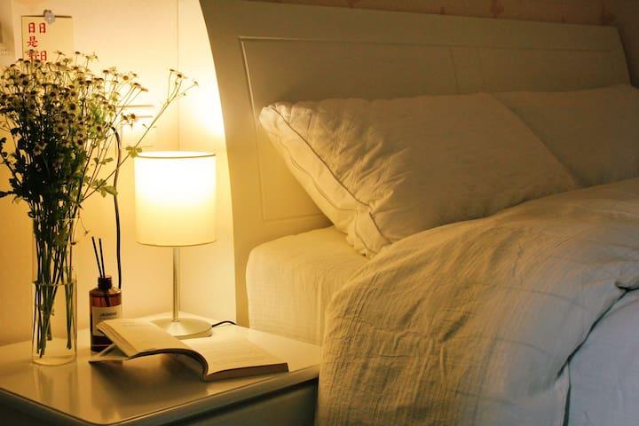 暖色床头灯、纯棉床单