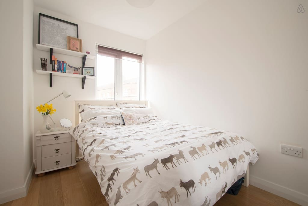 The comfortable double bedroom with bedside table and large built in wardrobe.