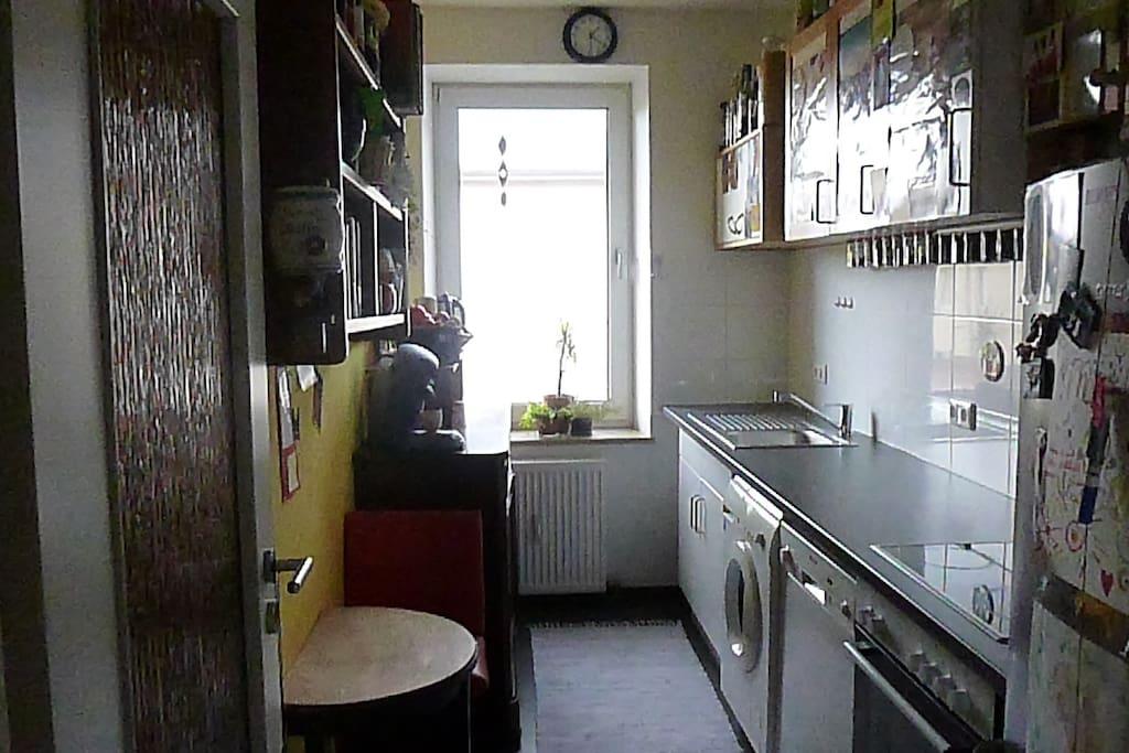 Küche mit Spühlmaschine, Ofen, Kühlschrank.