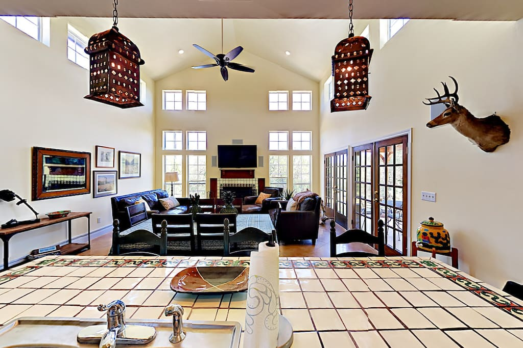 The living area with soaring ceilings and large windows that flood the space with light