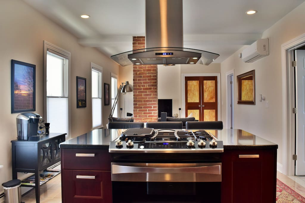 The island with a European style range hood and quartz countertop.