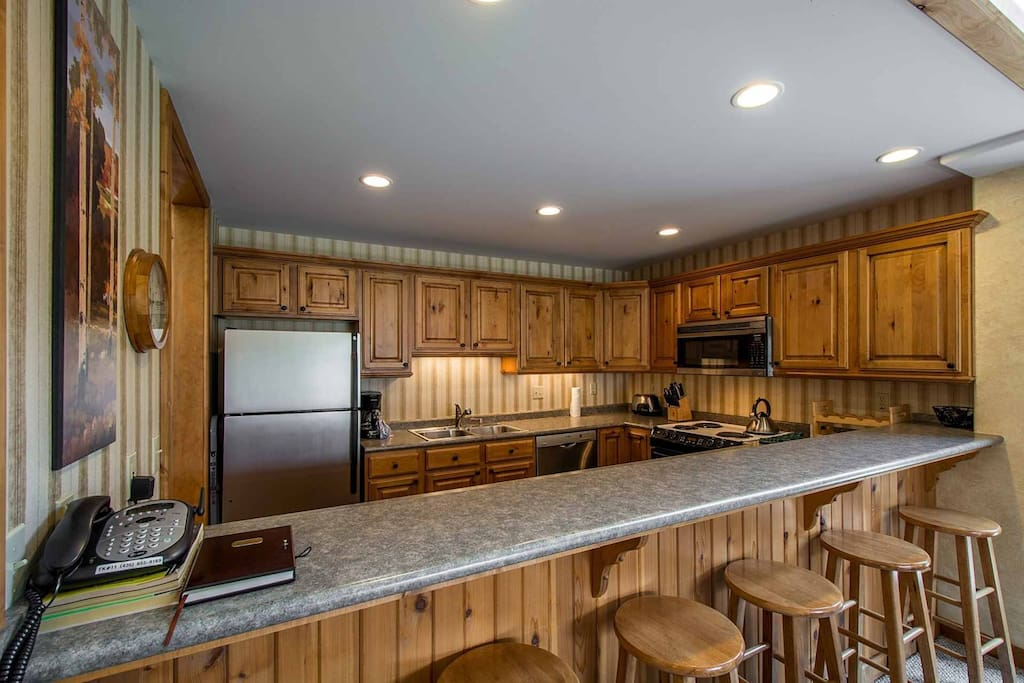 The kitchen also features hardwood cabinetry, tons of counter space and a large breakfast bar with seating for six (6).