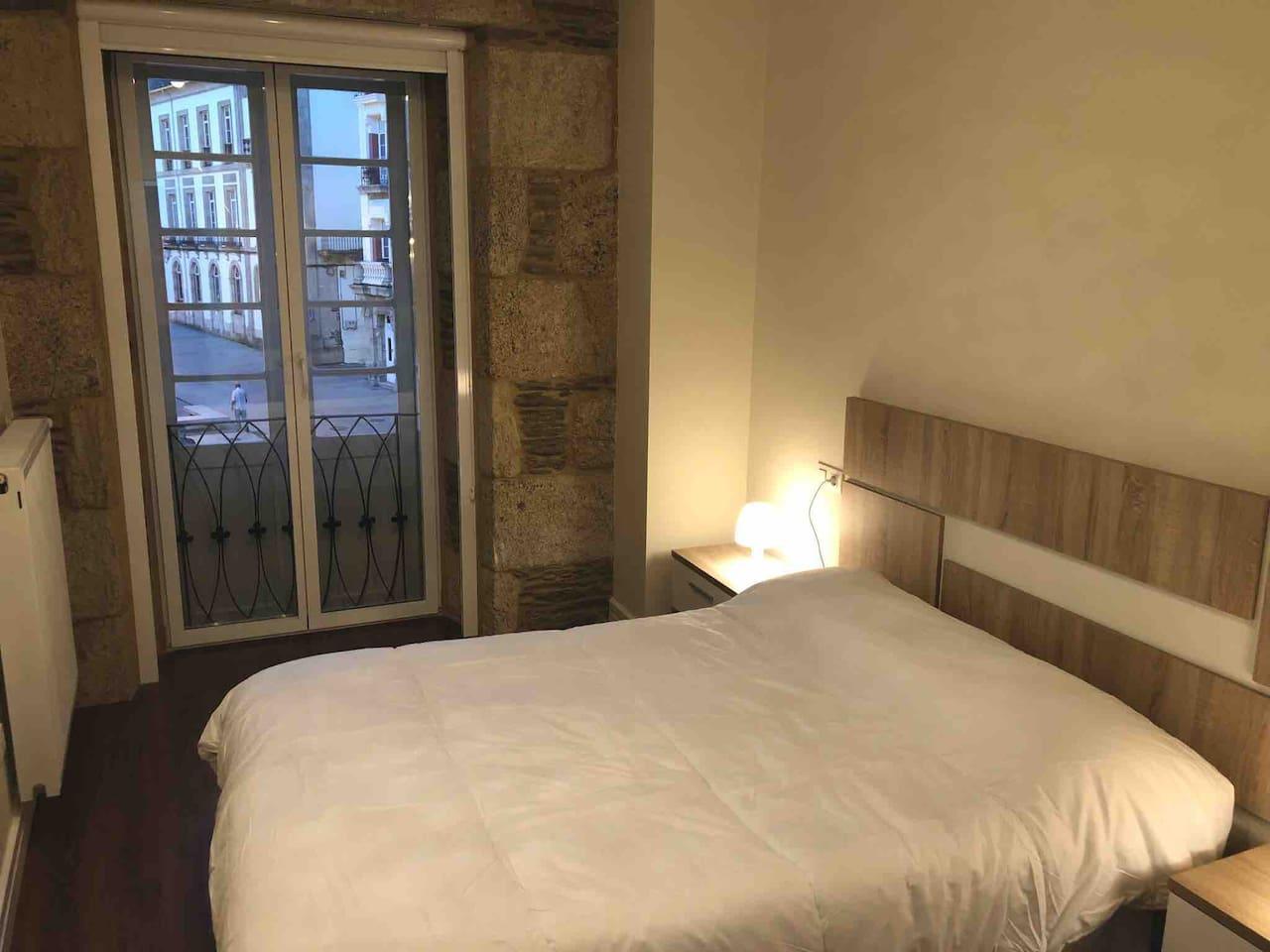 Habitación con cama matrimonial (135). Cuenta con lámparas en cada mesa de noche, armario y cómoda. Vistas a la Plaza Mayor.