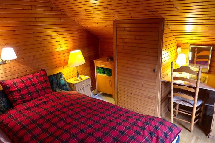 Kuschelig-cosy ist das Schlafzimmer mit Doppelbett und eingebauten Wandschränken. Es schliesst sich durch eine Verbindungdtür an das Wohnzimmer an.