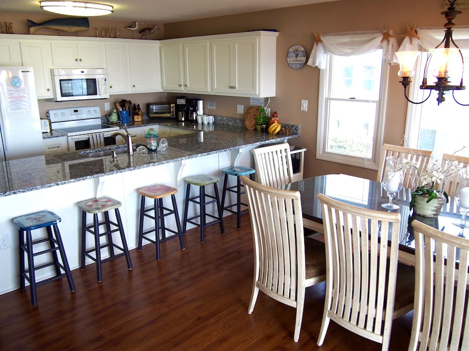 Open and airy kitchen and dining space - chat and look out at the ocean while you cook! Counter sits 5 and table sits 8. Room for everyone!!
