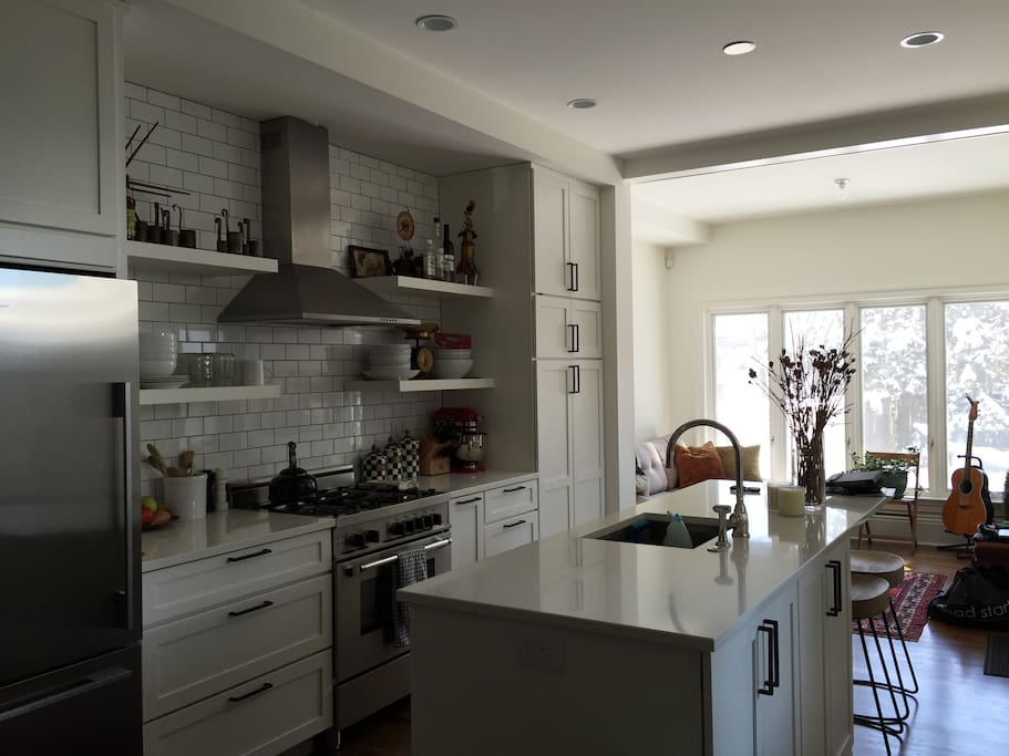 A cook's kitchen with island and counter stools.