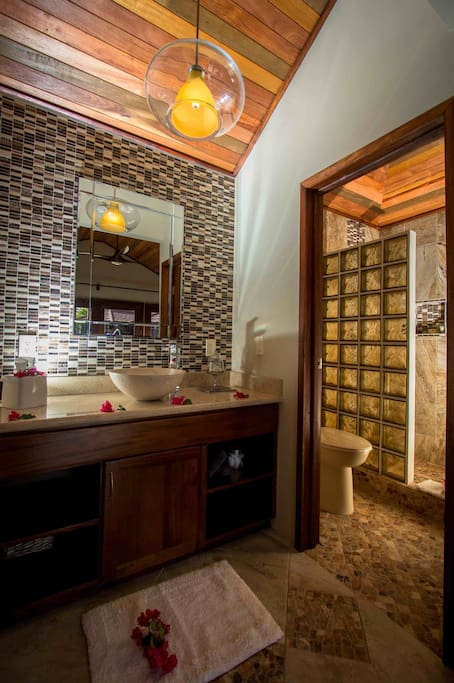 The bathroom features custom tile work, glass blocks and a rainwater shower.