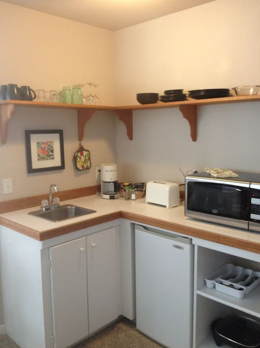 Kitchenette with coffee maker, microwave, refrigerator, toaster and electric skillet.