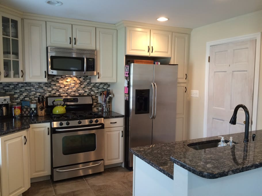 Kitchen, open to dining room. Gas stove, granite counters, fully stocked with dishes, cookware, bakeware.