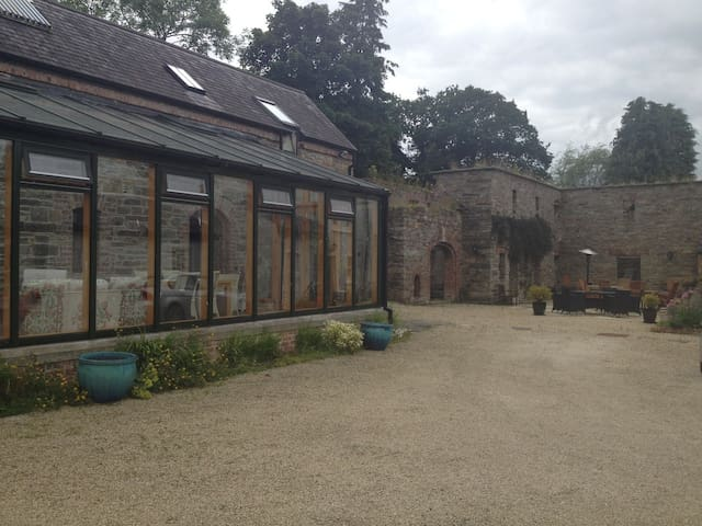 The exterior sun room viewed from the main farmyard surrounded by the former stone farm buildings.