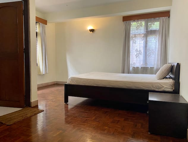 Main bedroom with en suite bathroom. Has a large wardrobe and queen bed with bedding and side table