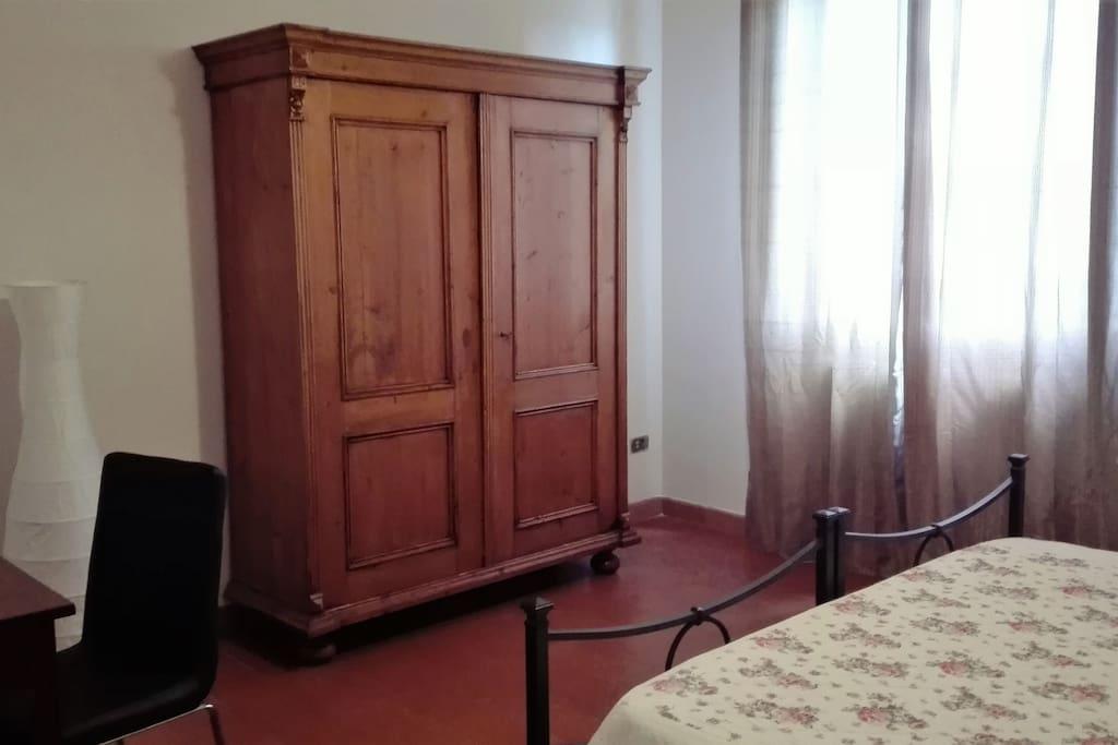 Camera matrimoniale con letto in ferro battuto, grande armadio, tavolo con sedia e specchio sopra al tavolo.