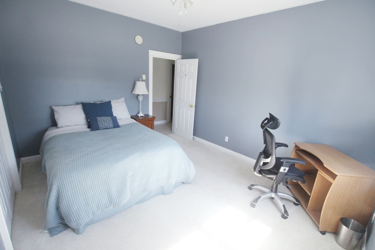 Queen size bed with a chair and desk work station.