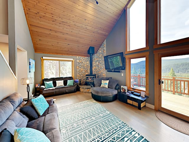Living room with 2 sofas, armchair, wood-burning stove, and flat screen TV.