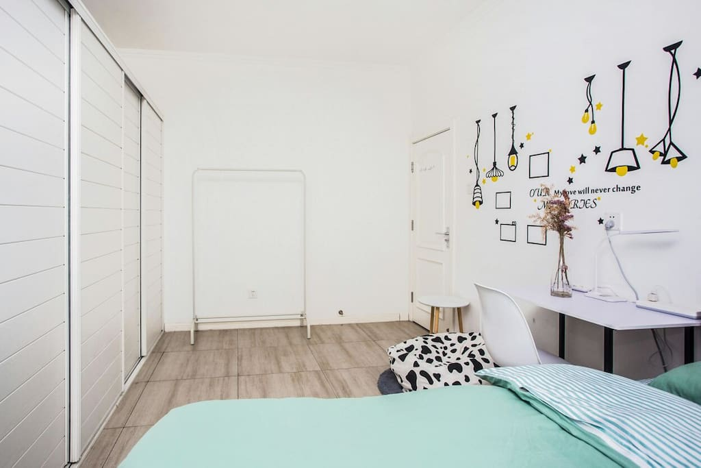 床对面超级多柜子,储物空间足足的,有书桌,有懒人沙发,有晾衣杆