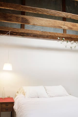 The bedroom has high ceilings like the rest of the house but with exposed old adobe and a skylight above the rafters.