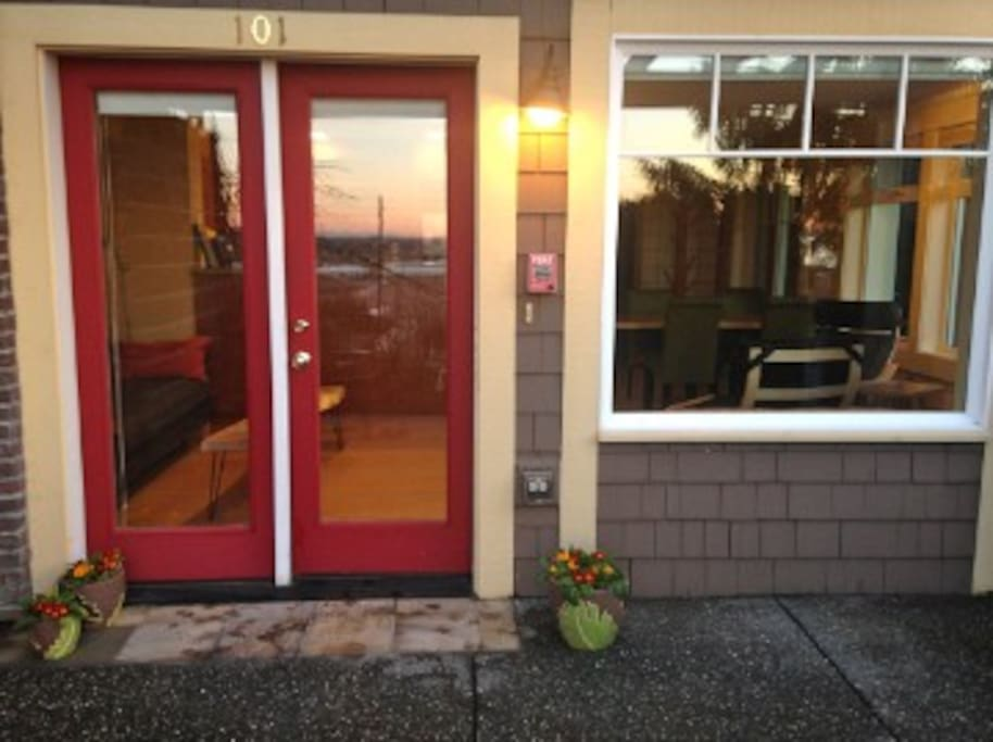 The Studio's main entrance, with sunset reflected in the glass. Summertime brings outdoor furniture for seating with a bay view.
