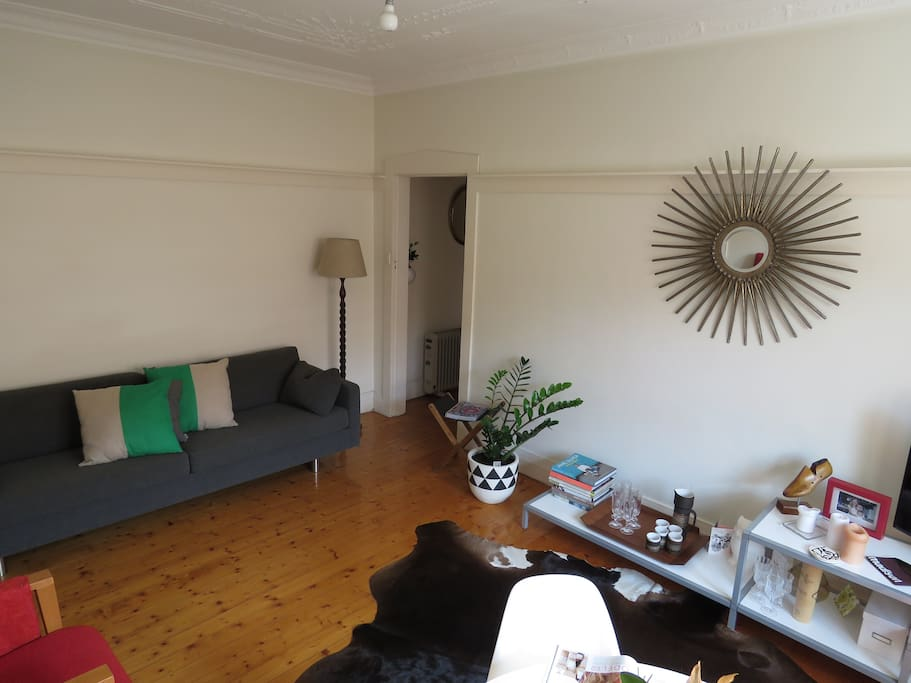 Bright living & dining area with TV, couch and armchair
