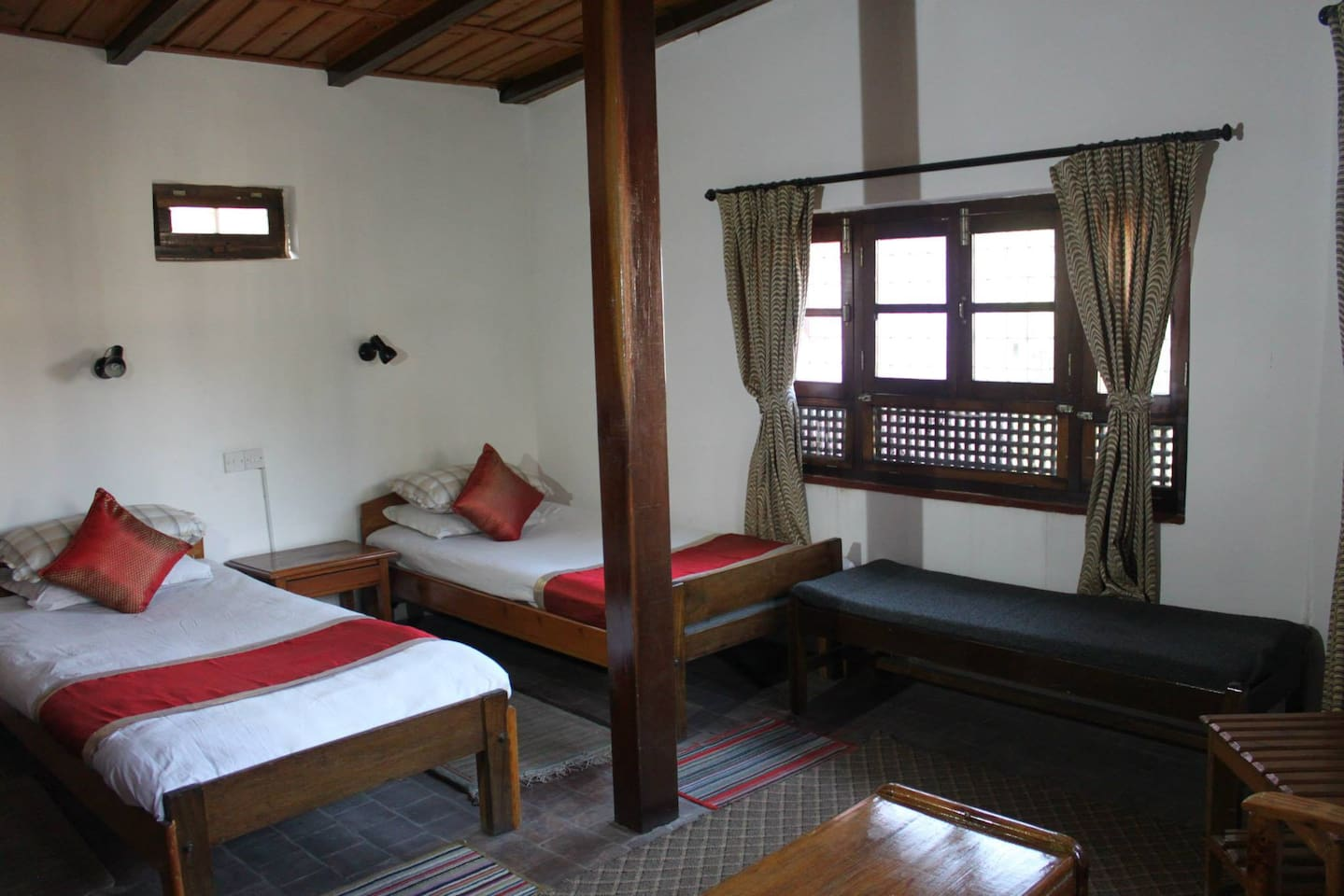 A twin room: a room with two beds for two guests and windows with garden views