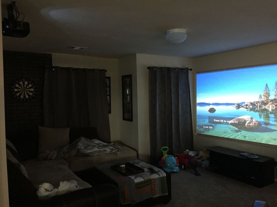 """Upstairs media room with 122"""" projection TV.  Awesome viewing experience.  Long sectional and recliner for lounging or sleeping additional guests."""