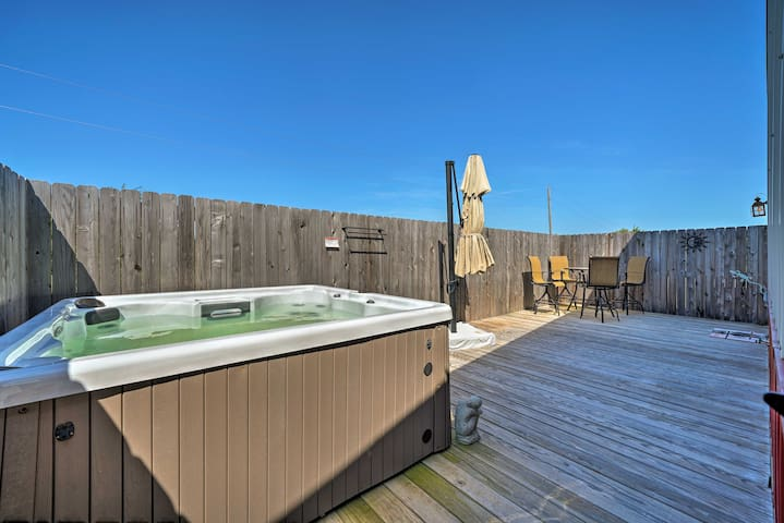 This 2-bed, 1-bath home includes a spacious wooden deck with a hot tub.