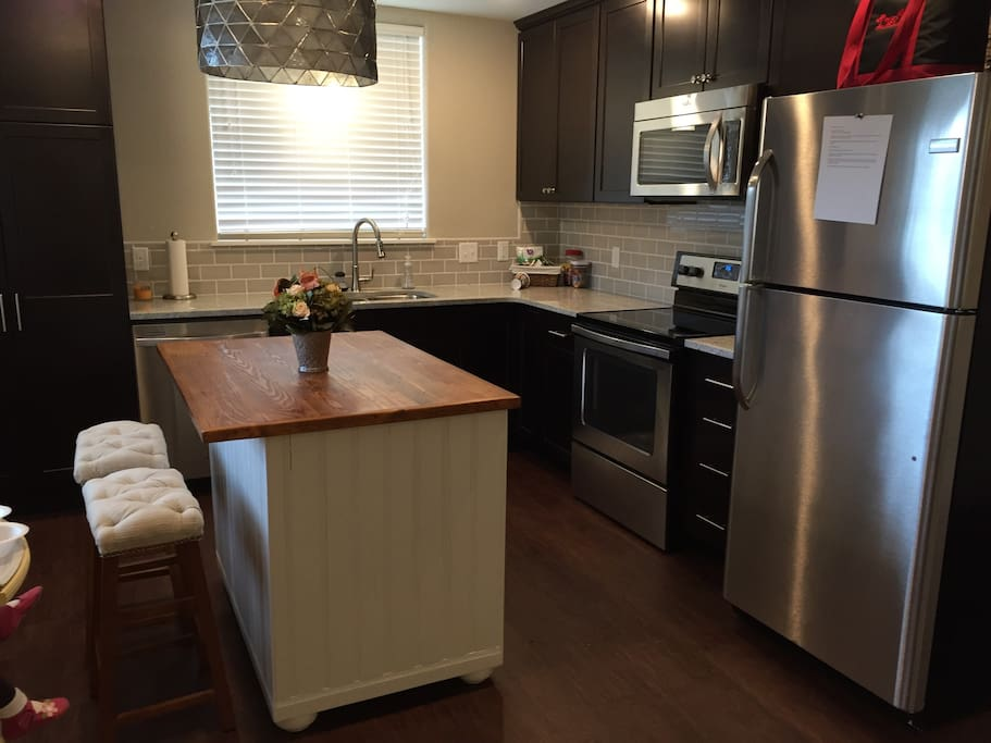 Full kitchen- dishwasher, range with oven/ceramic cooktop, full sized refrigerator with freezer and ice maker, microwave oven, island and pantry.