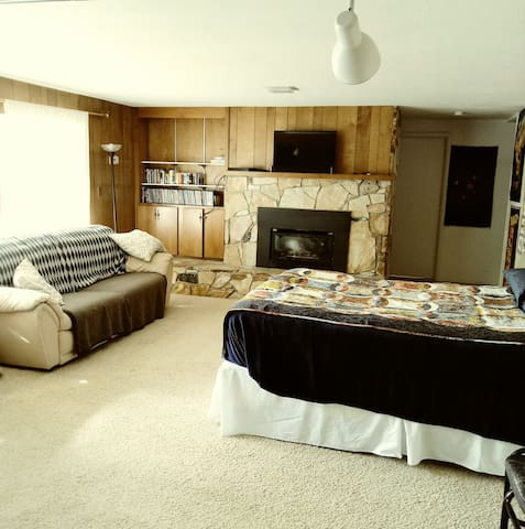 Spacious living room with comply couch, gas fireplace, TV, DVD, extra queen bed, outdoor views, and kitchenette with two tables and small refrigerator.