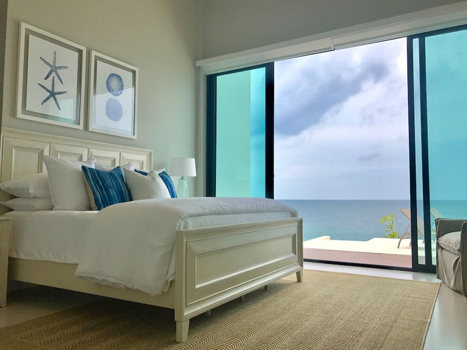 Master bedroom with king size bed and ocean view opens directly to yard and pool