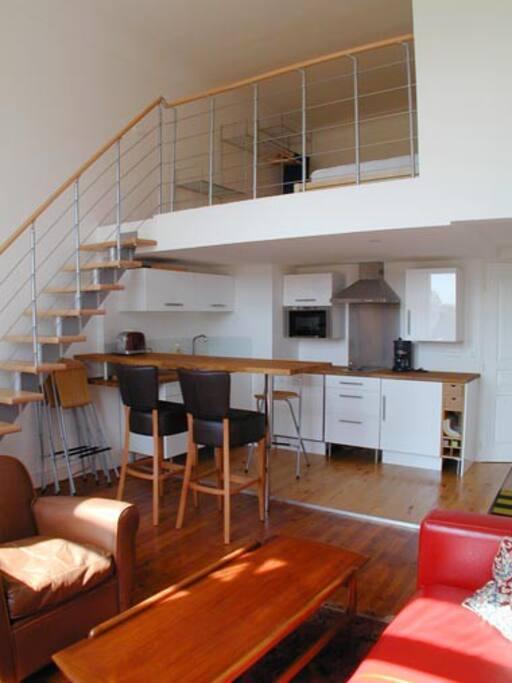 Cuisine américaine et escaliers montant vers la mezzanine