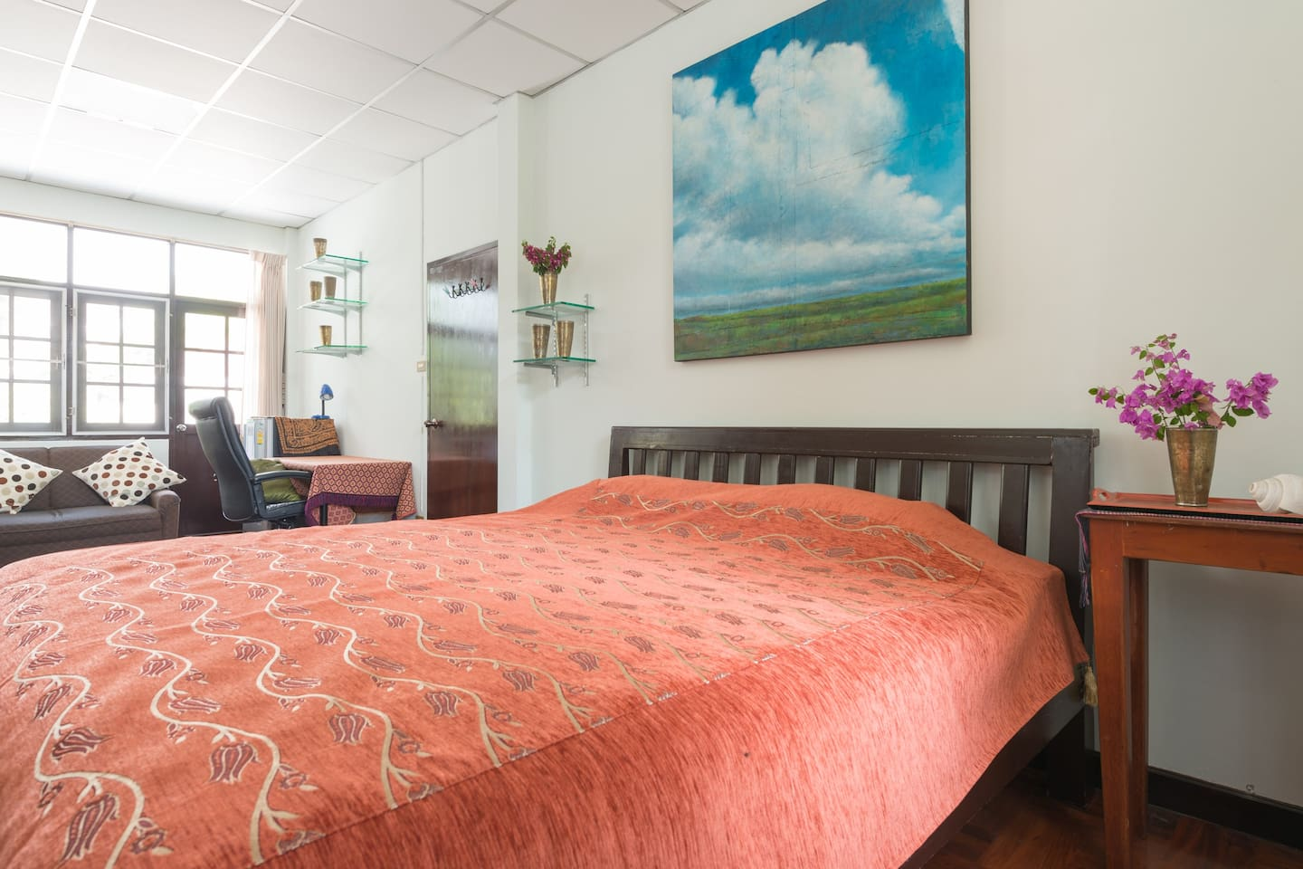 Large room with king size bed, TV, sofa, closet, balcony, working desk and refrigerator