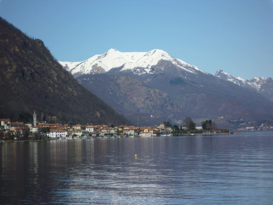 Panorama di Pella vista dal suo lago con le montagne innevate