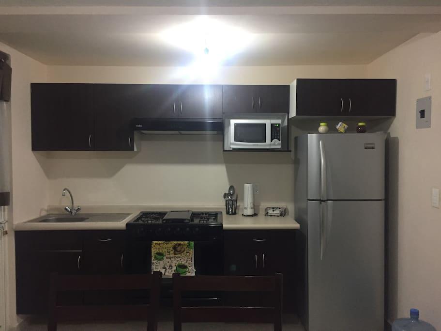 Cocina Integral con lo esencial para que puedas cocinar. Cuenta con microondas refrigerador estufa y horno.