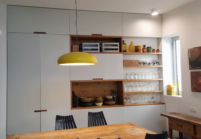 behind dining area cupboards with washing+drying machines, bar etc.