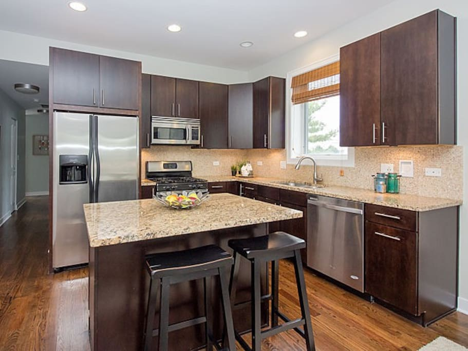 Modern kitchen with stainless steel appliances, dishwasher, and breakfast bar